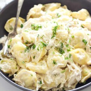 a black plate with tortellini and Chicken Alfredo