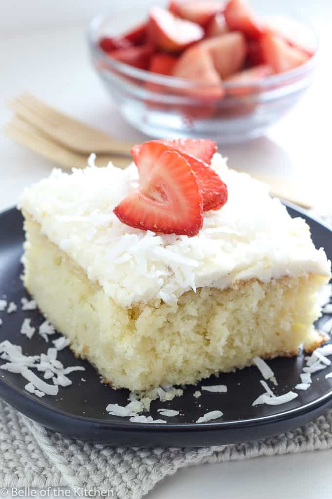 a slice of coconut cake on a black plate with strawberries on top