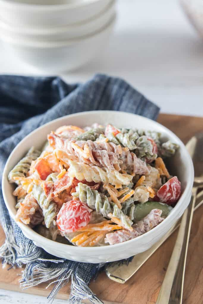 a bowl of pasta salad on a blue napkin