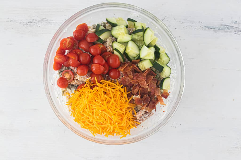 glass bowl with cheese, tomatoes, cucumbers, and bacon