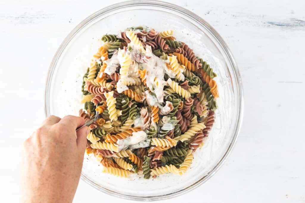 hand stirring pasta in a glass bowl