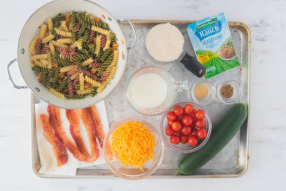 ingredients laid out to make pasta salad on a cutting board