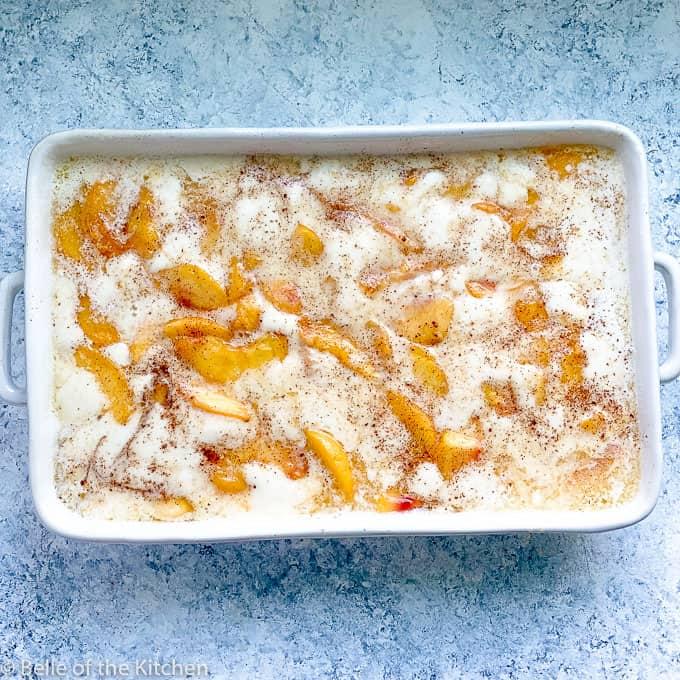 peach cobbler in a white baking dish