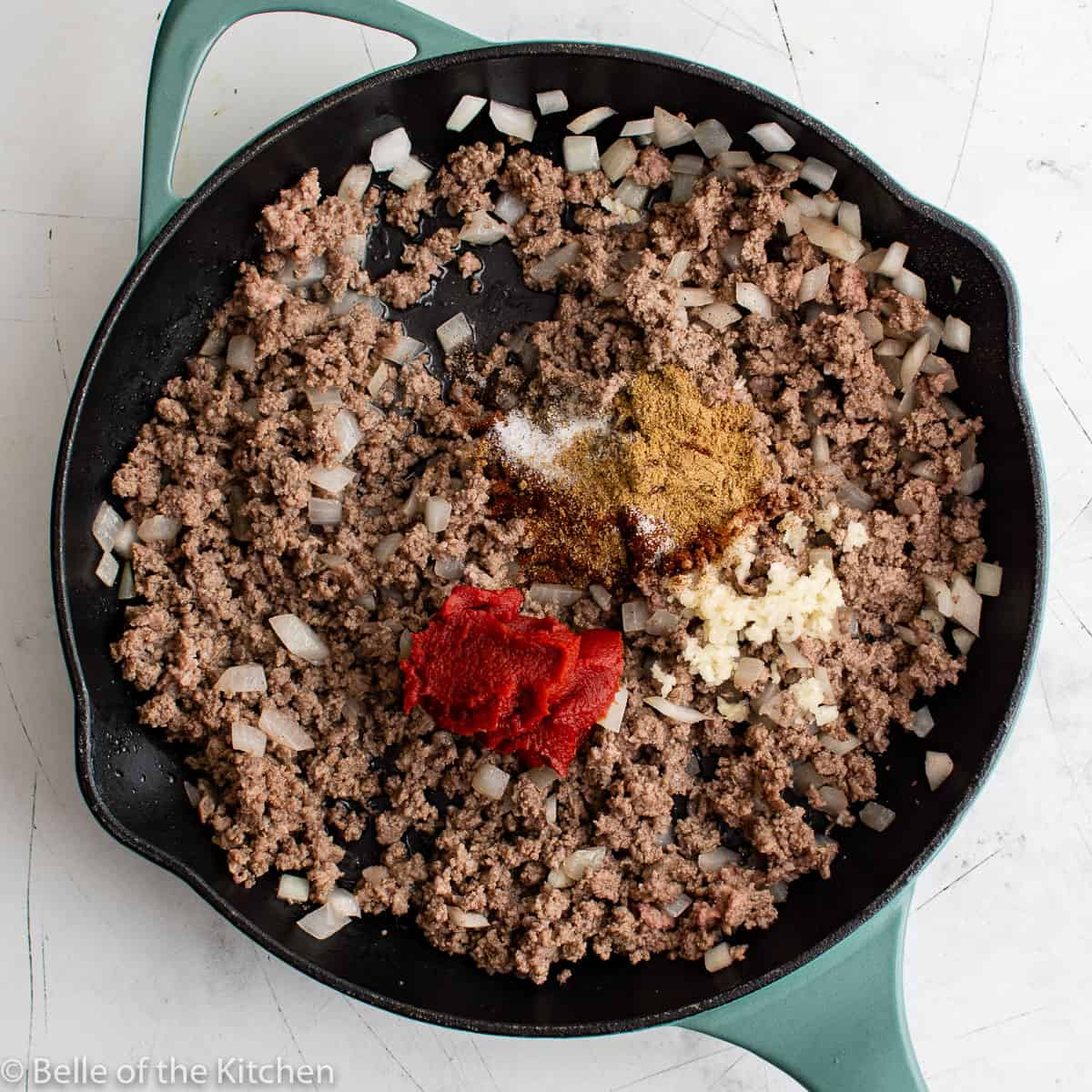 a skillet full of ground beef, onions, and spices