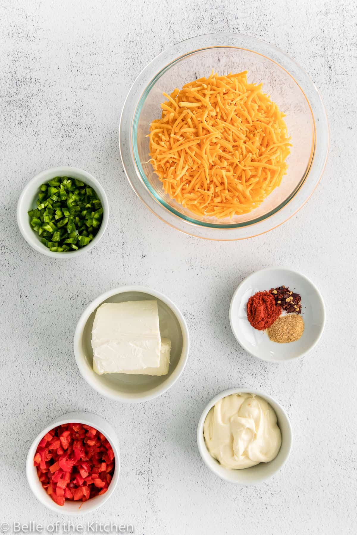 bowls of cheese, spices, mayo, cream cheese, and veggies