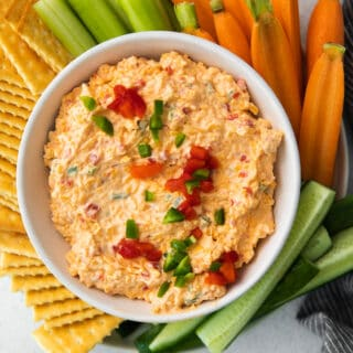 a bowl of pimento cheese with crackers and veggies around it