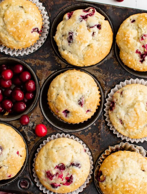 muffins in a muffin tin with fresh cranberries